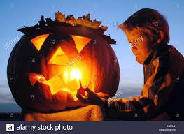 Origin Halloween Dpa Little Patrick Lights A Candle Inside A Halloween Pumpkin