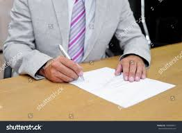 writing concept paper closeup businessman signing paper form concept stock photo close up of a businessman signing a paper form as a concept of acceptance of