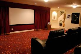 large screen on the wall added by red fabric curtains and black