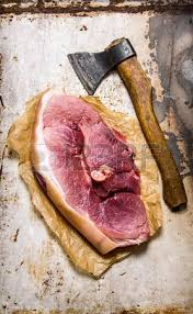 meat cutting table tops a piece of raw pork with a hatchet for meat cutting on the stone