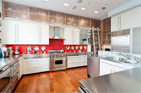kichen with white and stainless steel cabinets decorated with red