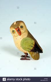 wooden owl ornament against a plain background stock photo