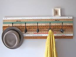 striped wooden coat rack base with black metal hook on grey wall