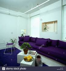 purple livingroom purple sofa along the length of a wall in white eighties