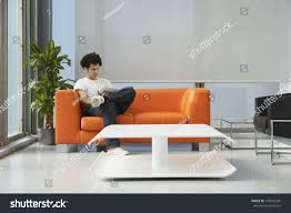 young man reading newspaper on orange stock photo 146047205