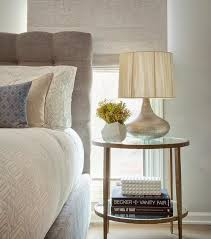 silver barrel side table chic bedroom features a gray button tufted headboard on bed dressed