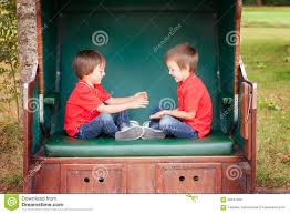 two kids sitting in a sheltered bench playing hand clapping ga