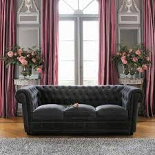 black chesterfield sofa with grey shag rug and flower vases