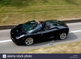 convertible lamborghini a black lamborghini convertible supercar driving fast along a road
