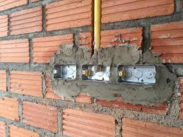 electric sockets installation in brick walls at house constructi