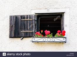 open window or hatch with red flowers in a flower box hanging