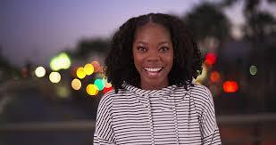 portrait of cute black female with pretty smile in urban setting