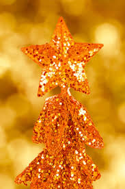 soft blur of light bokeh christmas tree and star at top over