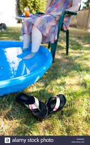 older woman in backyard with feet in small pool on a summer