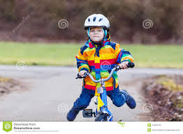 raincoat for bike riders funny cute preschool kid boy in safety helmet and colorful