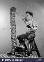 1950s Toaster 1950s Boy Eating Jelly Toast Sitting On Ladder Stacking Up Tall