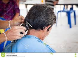 old man having a haircut with a hair clippers in barber shop stock