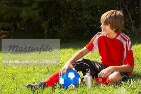 teenage speedo boys teenage boy in soccer uniform sitting on grass with soccer ball