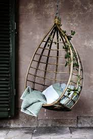 hanging outdoor egg chair with rattan material completed by pillow