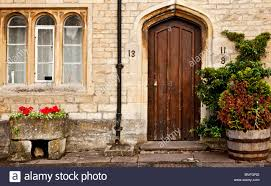 old wooden front door and mullioned window of typical old cotswold