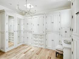 french white closet cabinets with whitewashed candle chandelier