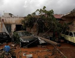 inside a destroyed cars are seen inside a yard following a heavy rainfall