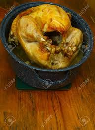 a fresh cooked thanksgiving turkey in a roasting pan on a wooden