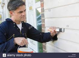 man holding brush and tin painting outside of house stock photo