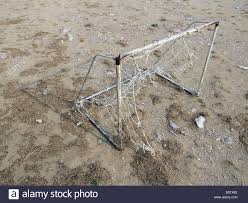 detail of old football goal posts in dirt field stock photo