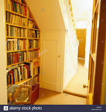 fitted bookshelves below staircase in an eighties hall stock photo