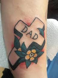 mens arm tattoo with a cross and