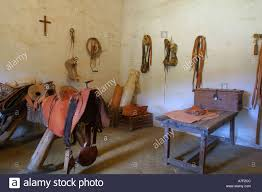 leather and wooden saddle in tack room at mission la purisima est