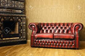 old red genuine leather sofa near the fireplace stock photo