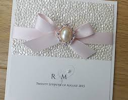 blush satin ribbon pebble sequin embossed paper with a gold pearl embellishment