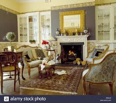 muted oriental rug and french sofa and armchairs in country living