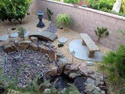 backyard with river rock walkway and small shrubs landscaping