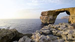 azure window colapse stone arch rock formation on a sea coast sunset on a summer time