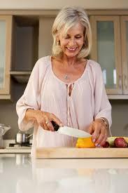 femme plus âgée heureuse dans la cuisine coupant les légumes frais