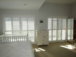 floor to ceiling full height shutters show off this modern house