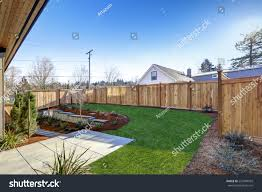 sloped backyard surrounded by wooden fence stock photo 557489959