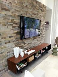 stone textured accent wall with wooden cabinet and wall mounted tv