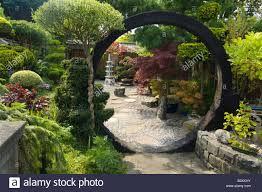japanese style garden with moon gate rocks shrubs and trees design
