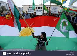 Kurdish Flag A Kurdish Protester Poses With A Small Kurdish Flag In Front Of A