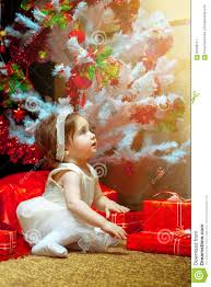 little baby sit under the christmas tree with a lot of gift