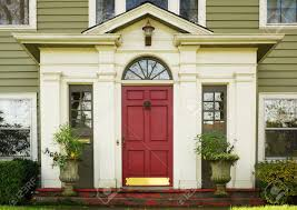 magenta home door bordered by two large potted plants stock photo