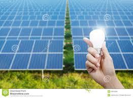 Solar Energy Lighting - solar energy panels and light bulb in hand energy stock photo