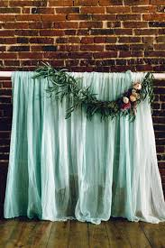 wedding backdrop fabric gauzy mint fabric backdrop with floral garland ruffled photo