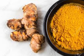 curcuma en cuisine of turmeric root or curcuma longa by bowl of turmeric powder