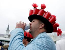 Kentucky Derby Flowers - race patron enjoys a drink under his hat of red beer cups filled