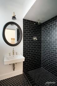 modern bathroom black subway tile brass fixtures white wall